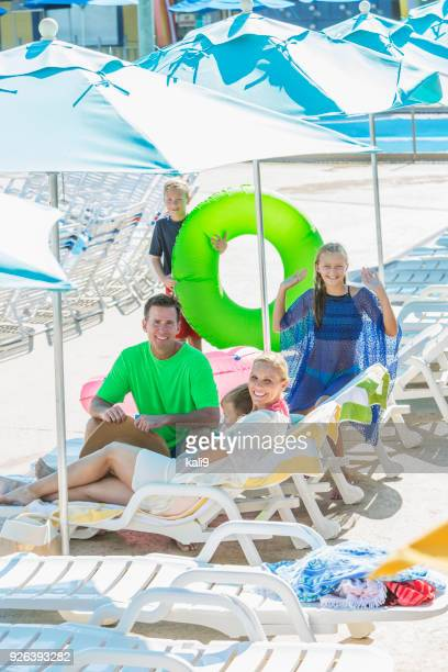 Family of five relaxing on pool deck lounge chairs
