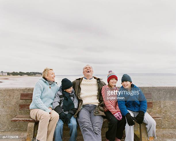 Family of Five Sit on a Wooden Bench By the Sea Having Fun