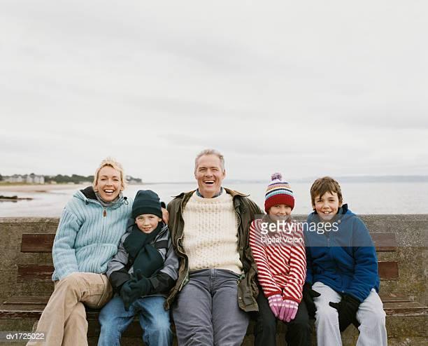 family of five sit on a wooden bench by the sea having - vijf personen stockfoto's en -beelden