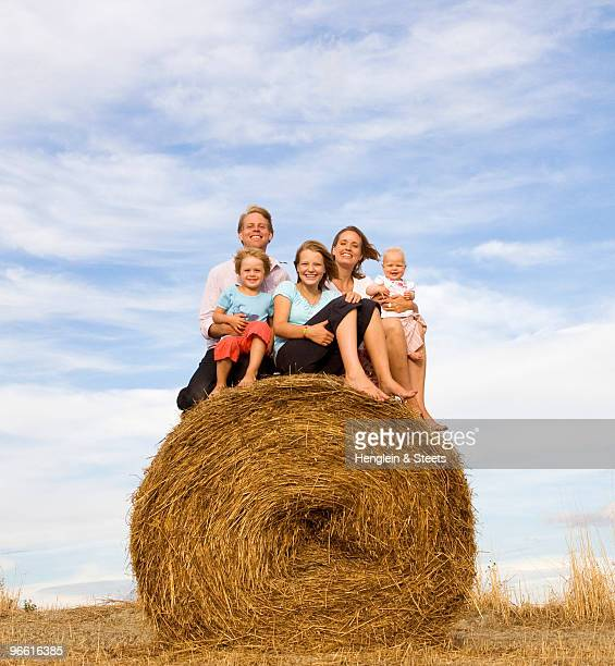 family of five sitting on hay bale