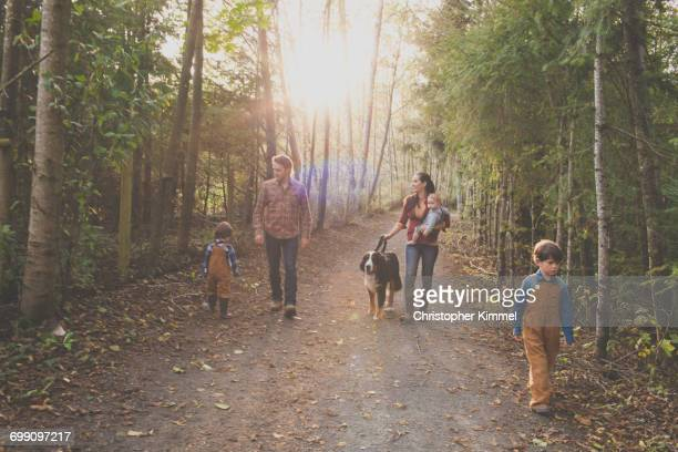 A family of five with a dog enjoy a morning walk on a gravel path at a local park.