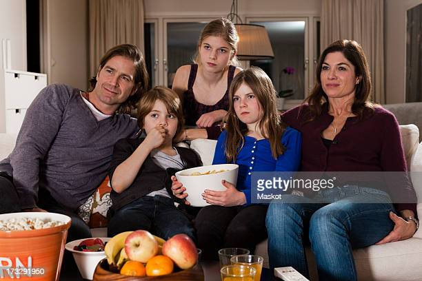 Family of five with bowl of chips watching television in living room
