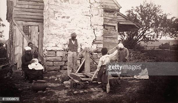A family of former slaves outside their ramshackle house in Fredericksburg Virginia ca 18621865