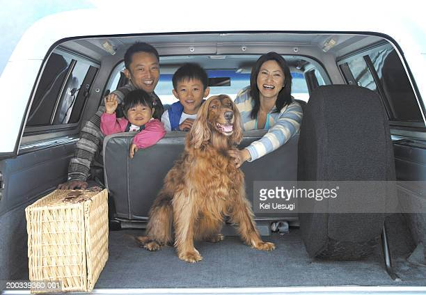 family of four and dog in back of car, portrait, view through boot - family inside car stock photos and pictures