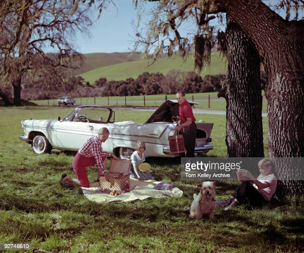 A family of four and their dog enjoy a day outdoors during a picnic Agoura CA 1958 in this advertisement for Plymouth Belvedere convertibles