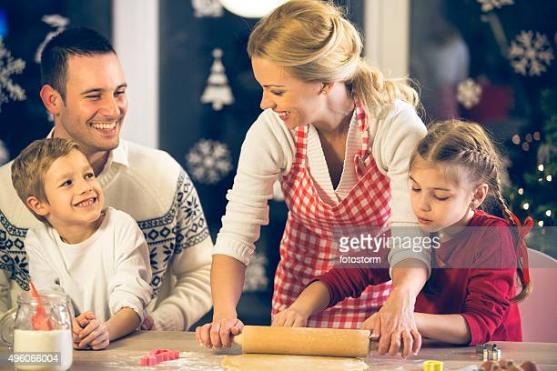 Family of four baking Christmas cookies together