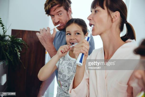 family of four brushing their teeth - electric toothbrush stock pictures, royalty-free photos & images