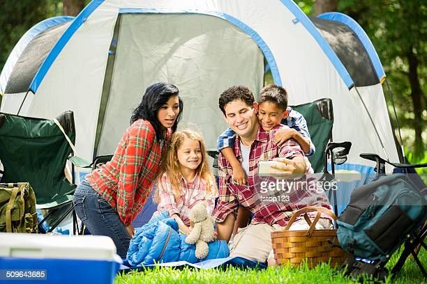 Family of four camping outdoors in forest. Tent. Taking selfie.