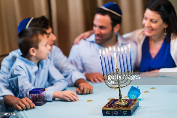 family of four celebrating hanukkah - hanukkah imagens e fotografias de stock
