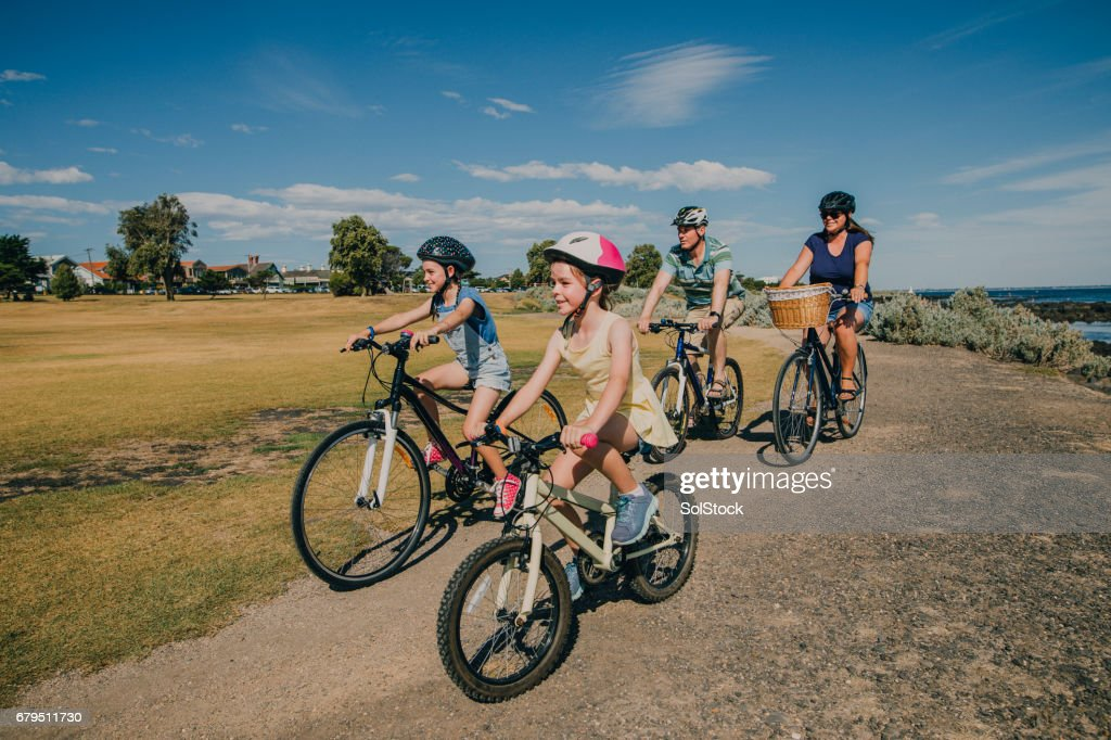 Family of Four Cycling in the Park : Stock Photo