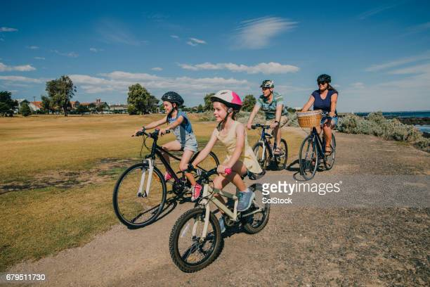 family of four cycling in the park - bicycle stock pictures, royalty-free photos & images
