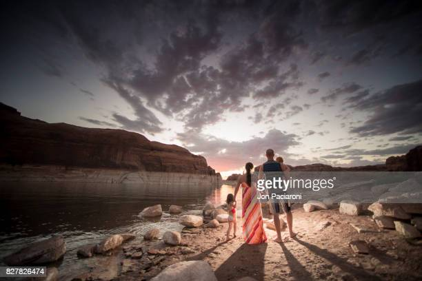 family of four enjoying a colorful sunset on the shorelines of lake powell - lake powell stock pictures, royalty-free photos & images