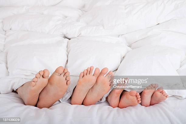Family of four feet in bed