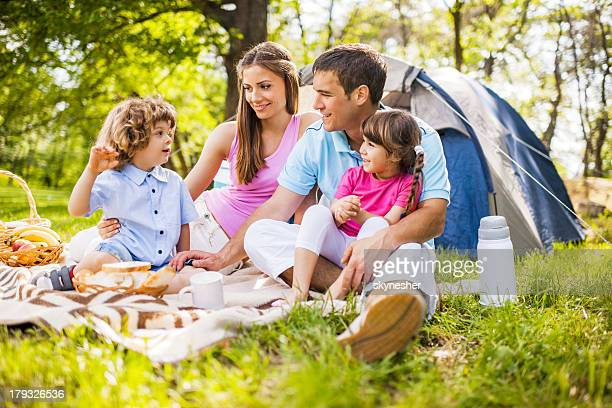 Family of four having a picnic in a grassy area
