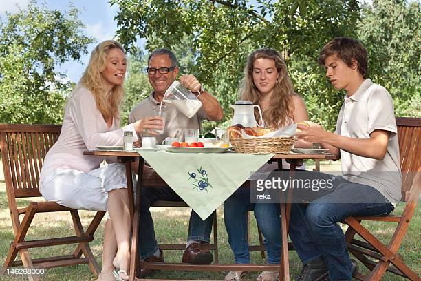 Family of four having breakfast at garden table