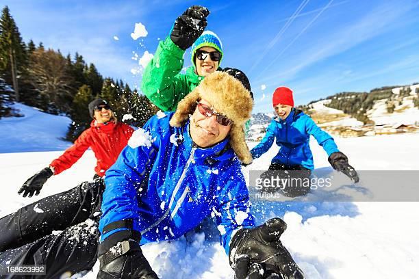 Famille de quatre personnes s'amuser dans la neige