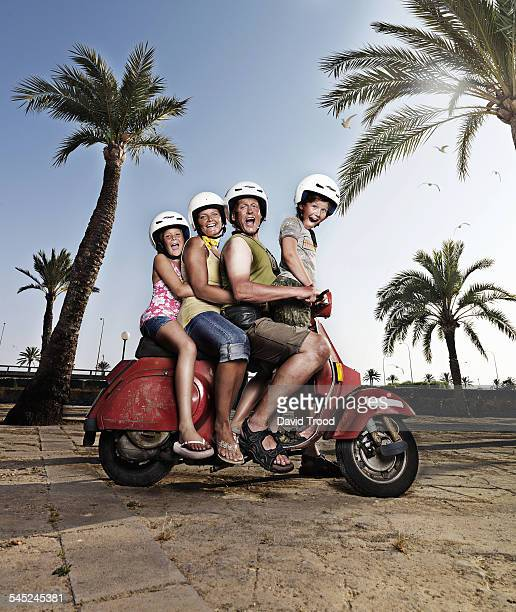 Family of four having fun on a moped