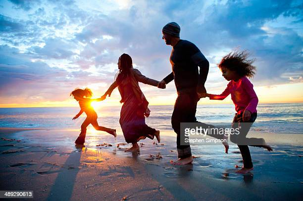 family of four having fun running on the beach