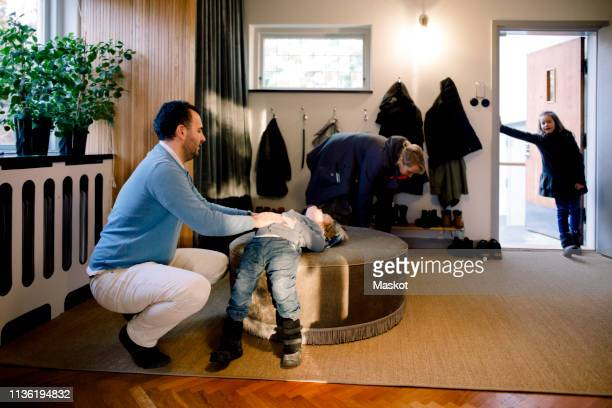 family of four in mudroom at home - warm clothing stock pictures, royalty-free photos & images