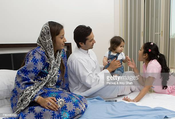 Family of four in the bedroom playing with baby