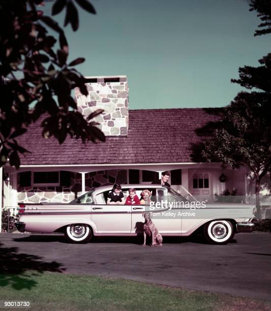 A family of four in their Mercury Monterey automobile on the driveway of their home 1959 Their pet dog sits next to the car