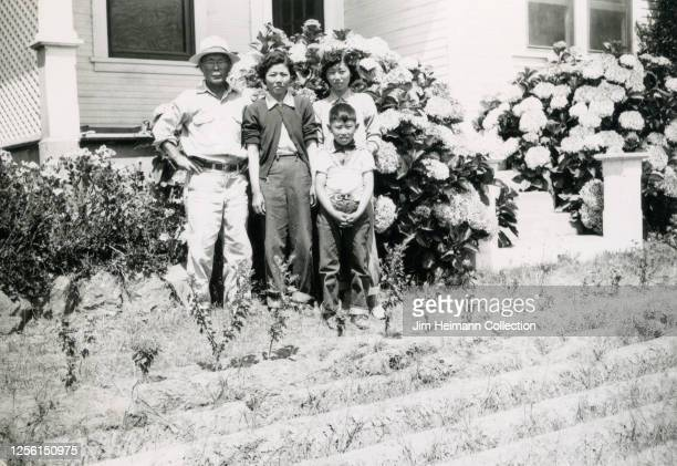 Family of four Japanese American famers stand in front of their home farm, which has crops in the front yard, in Southern California, circa 1940.