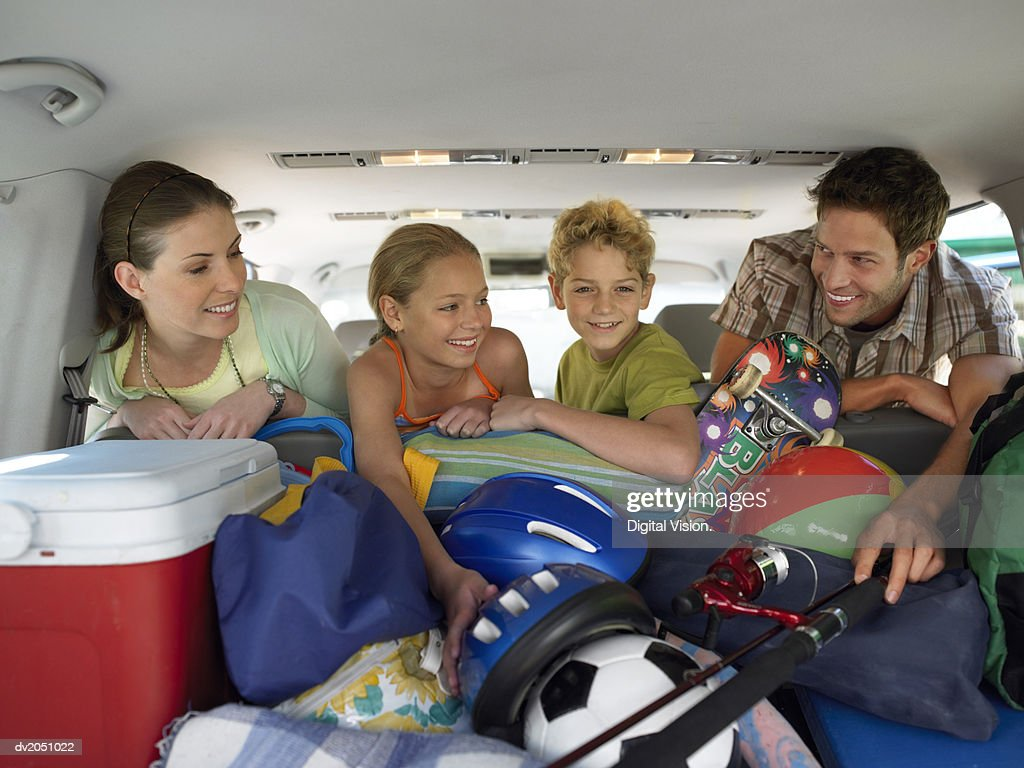 Family of Four Looking at Luggage in the Trunk of a Car : Stock Photo