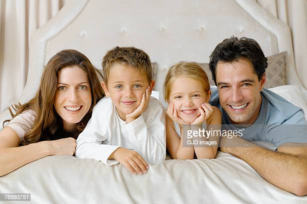 A family of four lying on a bed
