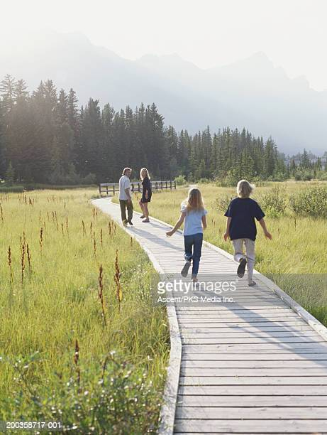 Family of four on boardwalk through meadow