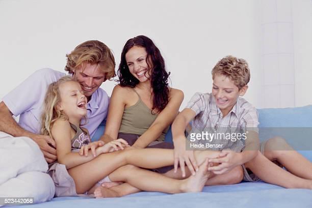 family of four on couch - fazendo cócegas - fotografias e filmes do acervo