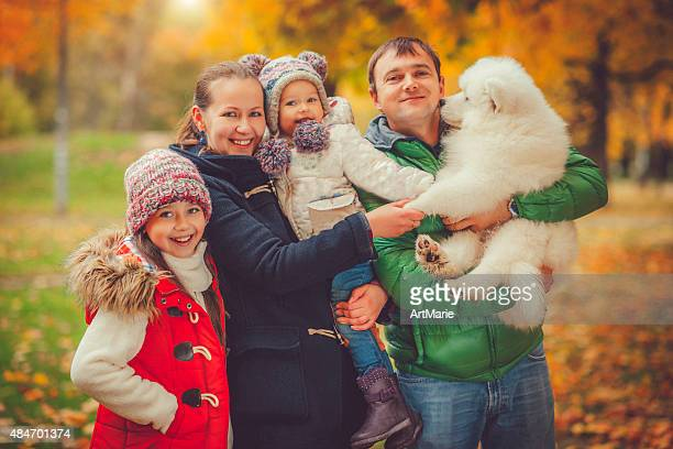 Family of four outdoors in autumn park