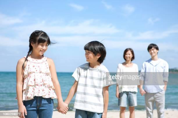 海辺に立つ4人家族 - 姉妹 ストックフォトと画像