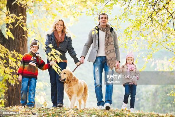 Famille de quatre personnes à un chien dans le parc.