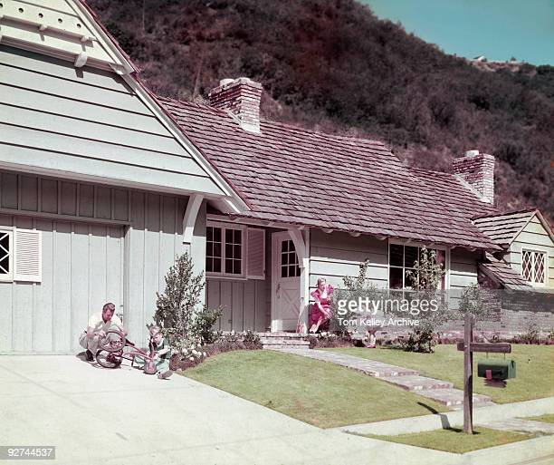 A family of four perform chores around their house in the San Fernando Valley CA 1950 The father is helping his son fix a tricycle while the mother...
