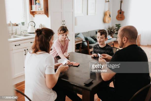 family of four playing cards in kitchen - carta de baralho jogo de lazer - fotografias e filmes do acervo