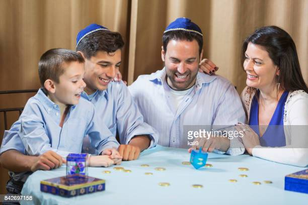 family of four playing dreidel game - hanukkah stock pictures, royalty-free photos & images