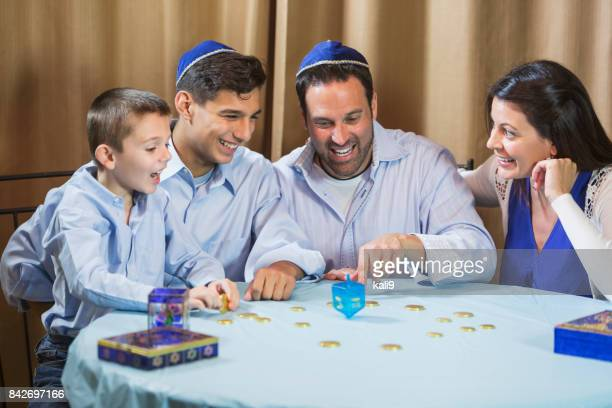 family of four playing dreidel game - dreidel stock photos and pictures