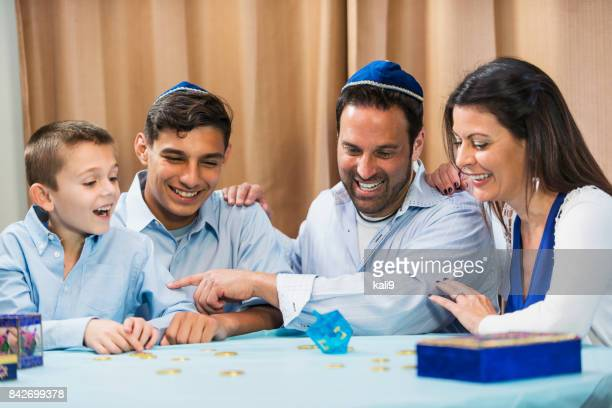 Family of four playing dreidel game