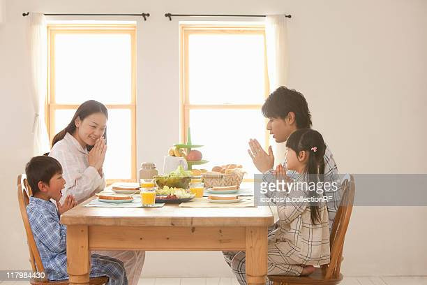 Family Of Four Praying at Breakfast Table