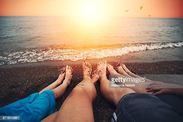 family of four relaxing on beach