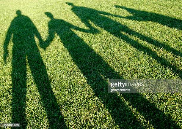 family of four shadows in the park - schaduw stockfoto's en -beelden