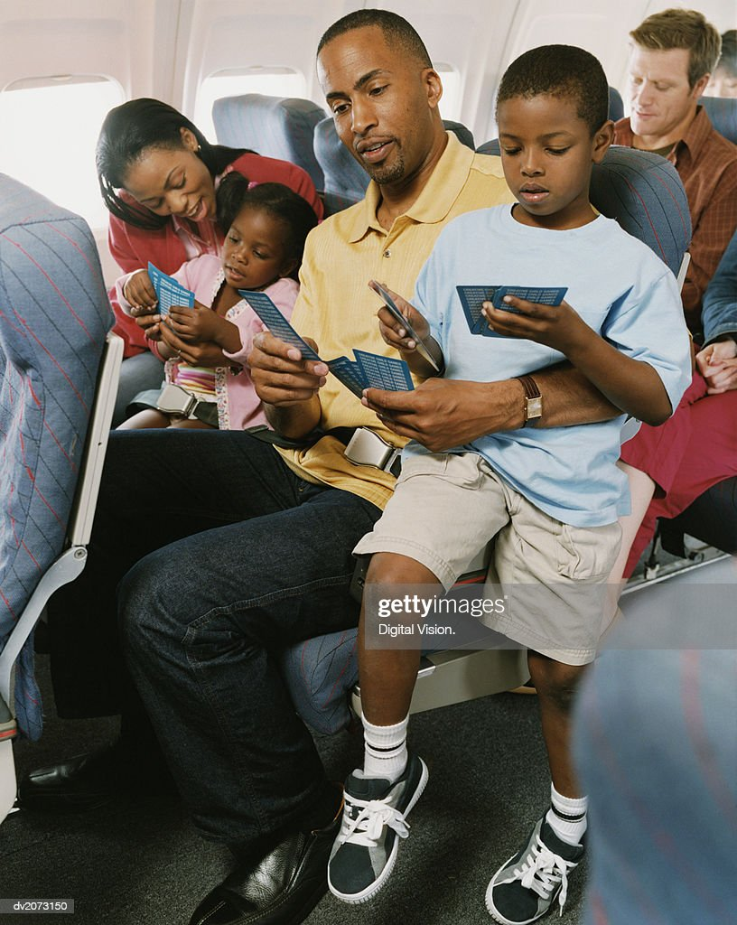 Family of Four Sit on a Plane, Playing Cards : Stock Photo