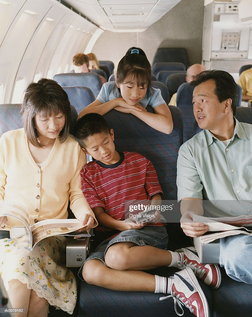 Family of Four Sit on a Plane, Reading Magazines and Playing Computer Games : Stock Photo