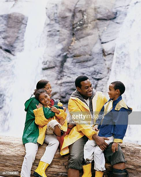 Family of Four Sitting on a Tree Trunk in Front of a Waterfall Talking