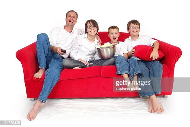 Famille de quatre assis sur le canapé en regardant un film en rouge