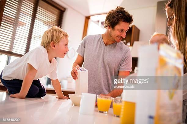 Familia de cuatro y erguida de su desayuno en la cocina