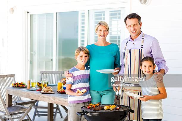 Family Of Four Standing By Barbecue On Patio