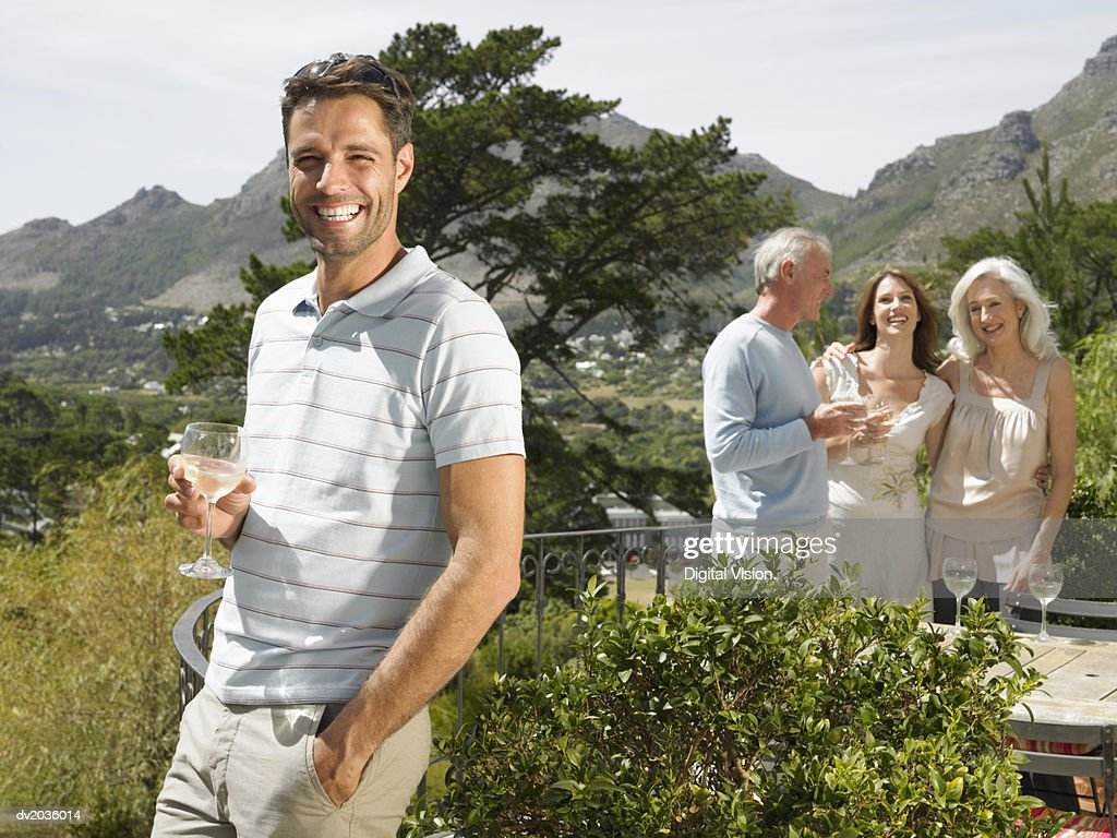 Family of Four Standing on a Terrace Enjoying a Glass of Wine : Stock Photo