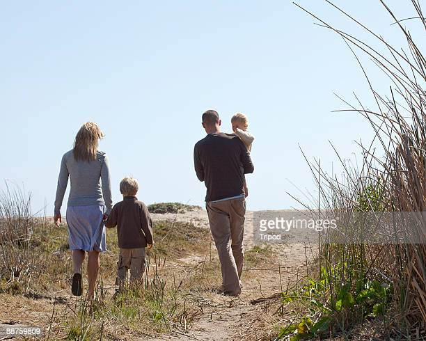 Family of four walking down path outdoors