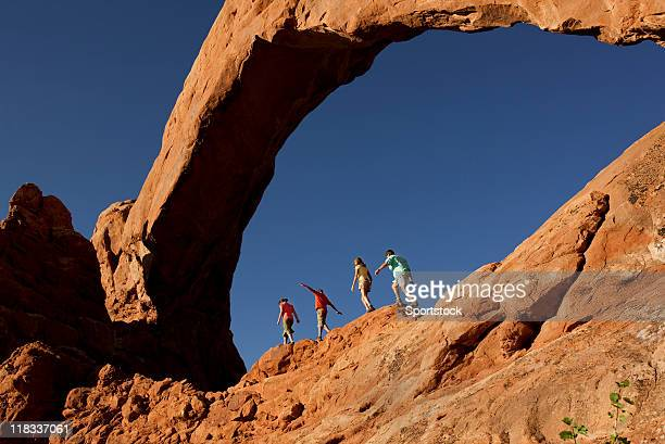 family of four walking on  rocks in arches national park - utah stock pictures, royalty-free photos & images